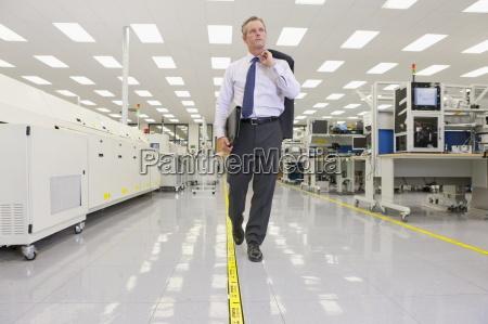 businessman walking through hi tech electronics