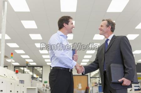 smiling businessmen shaking hands in hi