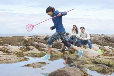familie exploring rockpools zusammen