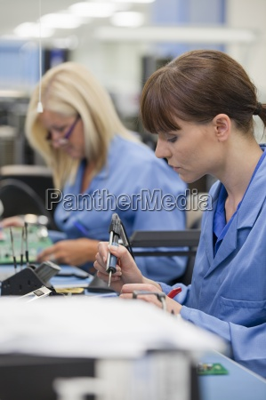technicians working on assembly line in