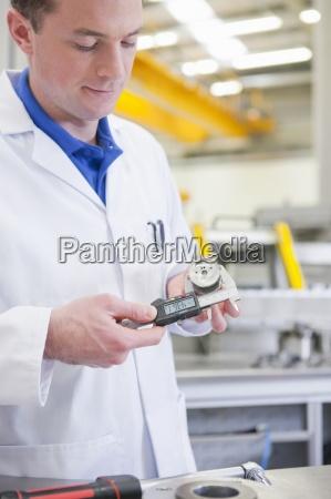 scientist measuring aluminum product with vernier