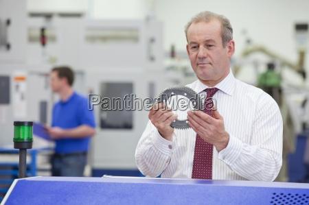businessman examining gear wheel in hi