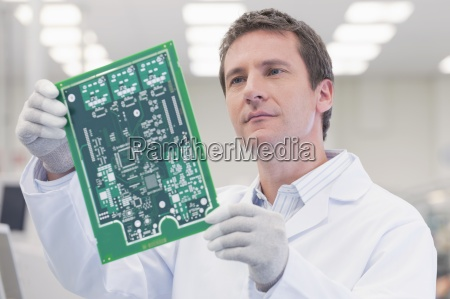 engineer examining printed circuit board in