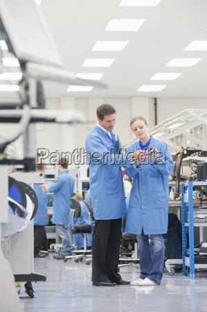 engineers examining machine part in manufacturing