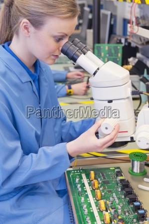 techniker mit mikroskop auf die leiterplatte
