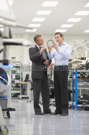 businessmen examining machine part in manufacturing