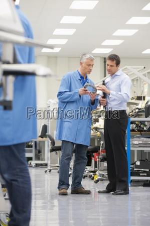 businessman and engineer examining machine part
