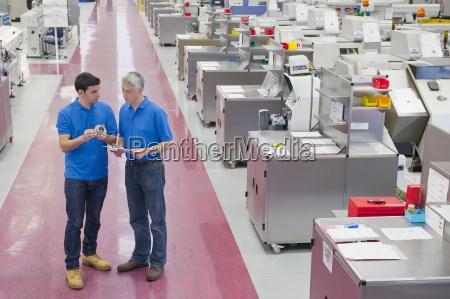 engineers examining machine part in aisle