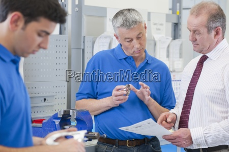 businessmen and engineers discussing machine part