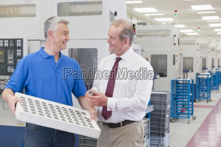smiling engineer and businessman examining finished