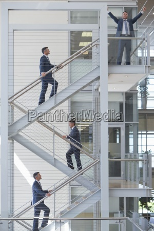 multiple image of businessman ascending stairs