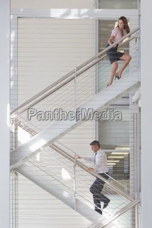 businessman and businesswoman on stairs in