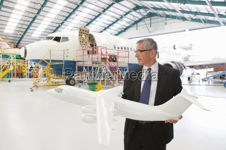 businessman holding model airplane in front