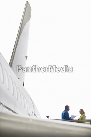 engineers talking at wing of passenger