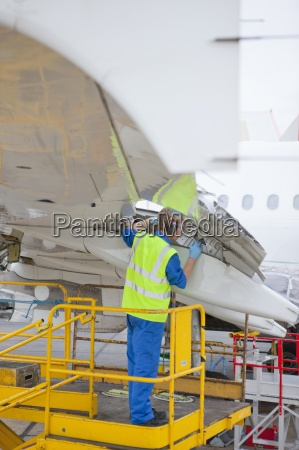engineer inspecting flap on wing of