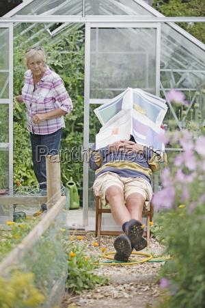 alter mann schlafend in gemuesegarten waehrend