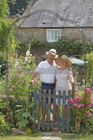 senior couple standing in garden of