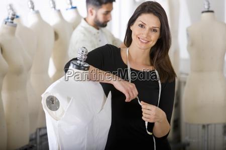 modedesigner auf kleid auf mannequin arbeiten