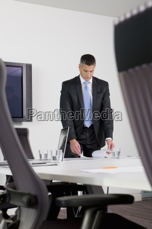 businessman reviewing paperwork on table in