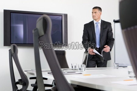 pensive businessman holding report at table