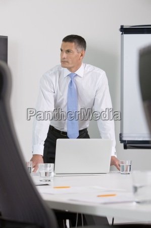 pensive businessman with laptop leaning on