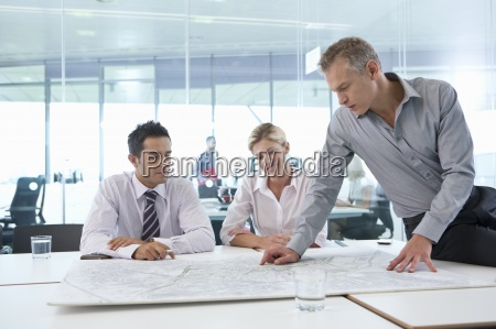 business people reviewing map in conference