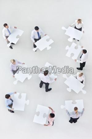 geschaeftsleute haelt grosse puzzleteile