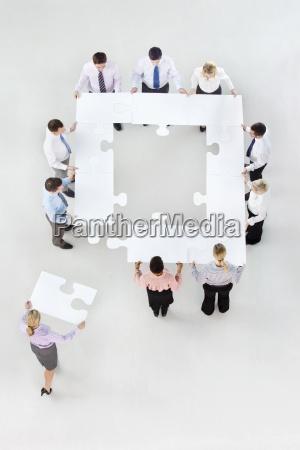 geschaeftsleute die quadratisch mit puzzleteile bilden