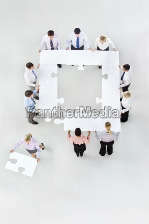 businesswoman removing jigsaw piece from square