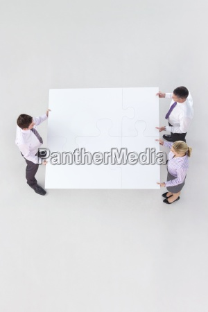 geschaeftsleute die grosse puzzlestuecke verbinden