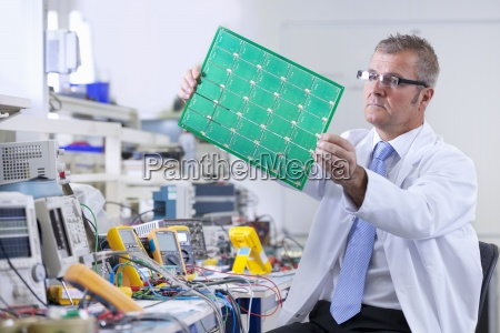 ingenieur prueft leiterplatte am elektrischen pruefstand