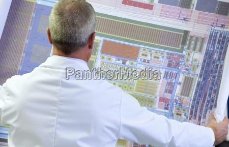engineer examining circuit diagram in laboratory