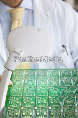 engineer examining circuit board under magnification
