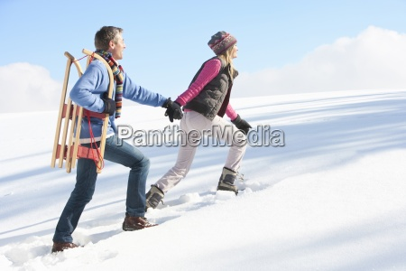 couple with sled holding hands and