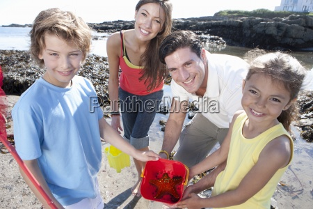 portrait of smiling family holding pail
