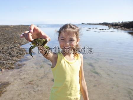 laechelnde maedchen haelt kleine krabbe am
