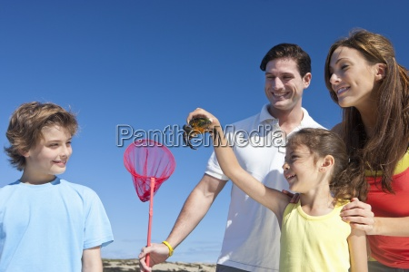family with fishing net holding crab