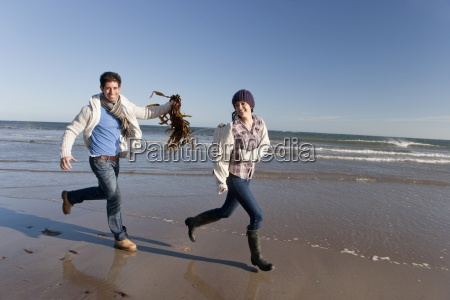 man holding seaweed and chasing woman