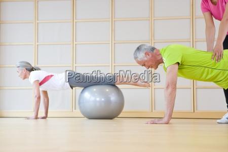 personal trainer helfen aelterer mann balance