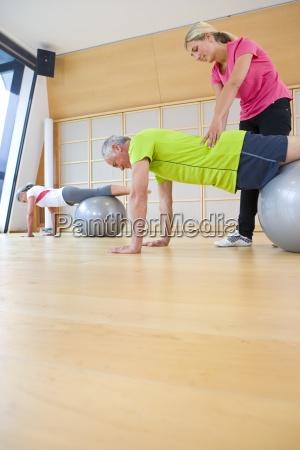 personal trainer helping senior man balance