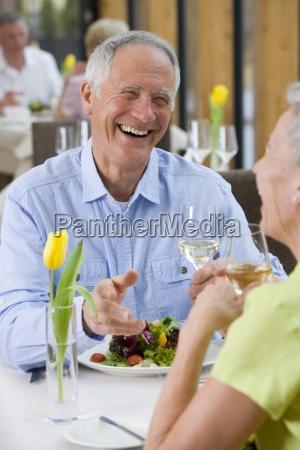 glueckliches paar trinken weisswein und salat