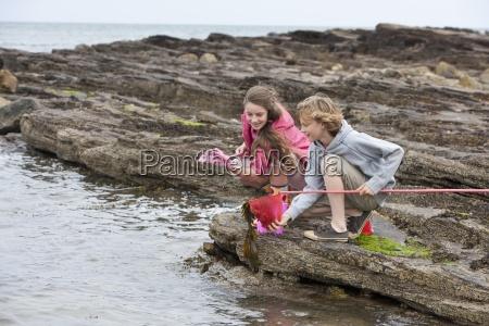 boy and girl fishing on rocks