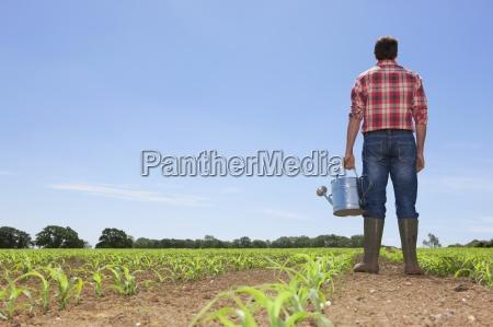 farmer mit giesskanne im feld von