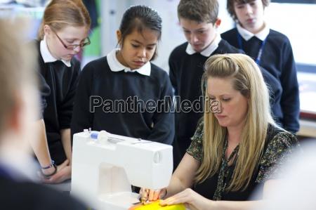 students watch teacher use sewing machine