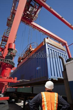 arbeiter beobachten kranlast fracht container auf