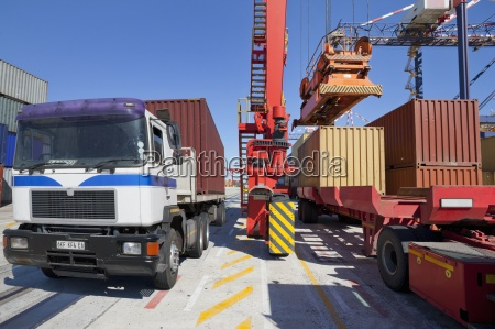 crane loading cargo container onto lorry