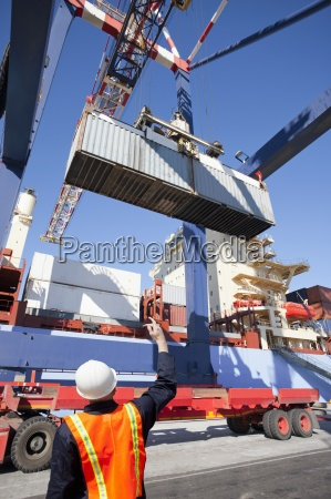 worker guiding crane with cargo container