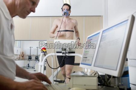 sportwissenschaftler an computer und laeufer mit