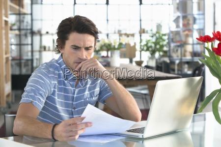ernster mann mit laptop zu papierkram