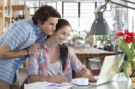 smiling couple using laptop at kitchen